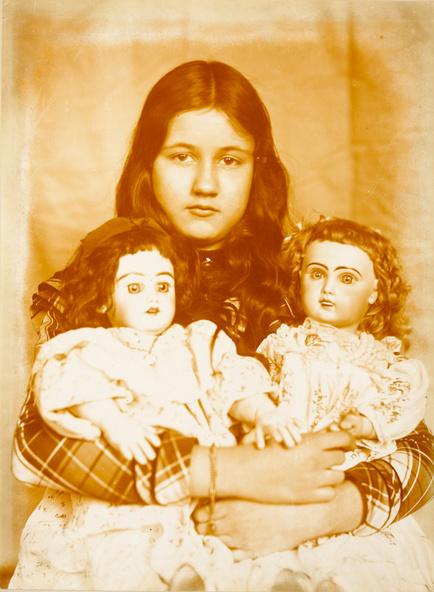 Emile Zola-Denise assise, deux poupées serrées dans les bras